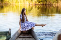 Lifestyle portrait of young beautiful woman sitting at motorboat. girl having fun at boat on the water royalty free stock photography