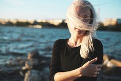Lifestyle portrait of young blonde woman in windy day at sea. Sunset light royalty free stock photo
