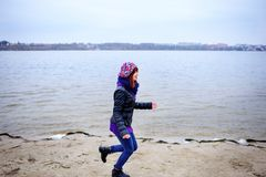 Lifestyle portrait of young Caucasian slim woman runs along beach autumn royalty free stock photography