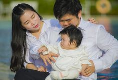 Cheerful and sweet wife and husband couple with mother holding baby girl and man playing with little daughter in Asian Korean stock photography