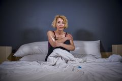 Lifestyle portrait of young desperate pregnant woman using pregnancy test sad and depressed for positive result expecting unwanted stock image