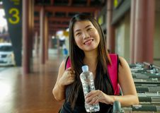 Lifestyle portrait of young happy and attractive Asian Chinese woman with backpack smiling excited and playful at airport arrival stock photos