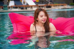 Young happy and attractive Asian Chinese woman enjoying at holidays resort swimming pool having fun in airbed smiling cheerful in. Lifestyle portrait of young stock photos