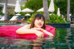 Young happy and attractive Asian Chinese woman enjoying at holidays resort swimming pool having fun in airbed smiling cheerful in. Lifestyle portrait of young royalty free stock photos