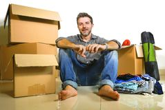 Lifestyle portrait young happy and attractive man unpacking cardboard boxes and belongings moving alone to new apartment in. Property investment and real estate royalty free stock image