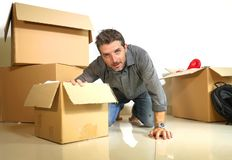 Lifestyle portrait young happy and attractive man unpacking cardboard boxes and belongings moving alone to new apartment in. Property investment and real estate stock photos