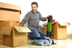 Lifestyle portrait young happy and attractive man unpacking cardboard boxes and belongings moving alone to new apartment in. Property investment and real estate royalty free stock photo