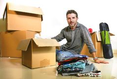 Lifestyle portrait young happy and attractive man unpacking cardboard boxes and belongings moving alone to new apartment in. Property investment and real estate stock images