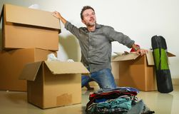 Lifestyle portrait young happy and attractive man unpacking cardboard boxes and belongings moving alone to new apartment in. Property investment and real estate royalty free stock images