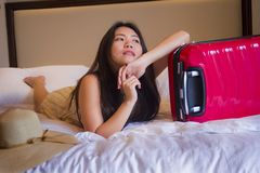 Young happy and beautiful Asian Korean tourist woman with travel suitcase just arrived at five star hotel room playing on bed. Lifestyle portrait of young happy stock photography
