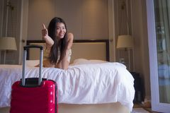 Young happy and beautiful Asian Korean tourist woman with travel suitcase just arrived at five star hotel room playing on bed. Lifestyle portrait of young happy stock image