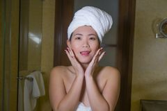 Young happy and beautiful Asian Korean woman at home bathroom with towel head wrapped washing face smiling cheerful and carefree t. Lifestyle portrait of young stock photo