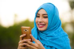 Lifestyle portrait of young happy and beautiful tourist woman in muslim hijab head scarf using mobile phone outdoors smil. Ing cheerful in holidays travel and stock images