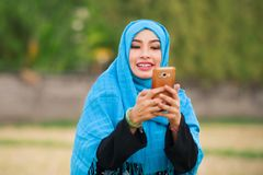 Lifestyle portrait of young happy and beautiful tourist woman in muslim hijab head scarf using mobile phone outdoors smil stock photos