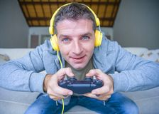 Lifestyle portrait of young happy and excited gamer man with headphones playing video game at home having fun on sofa couch holdi royalty free stock photo