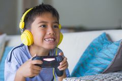 Young Latin little child excited and happy playing video game online with headphones holding controller having fun sitting on couc stock photography