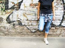 Lifestyle portrait of young person against colorful urban brick wall background. Lifestyle cropped portrait of stylish young person in casual clothes: black t Stock Image