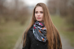Lifestyle portrait of young and pretty adult woman with gorgeous long hair posing in city park with shallow depth of field Royalty Free Stock Image