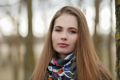 Lifestyle portrait of young and pretty adult woman with gorgeous long hair posing in city park with shallow depth of field Stock Images
