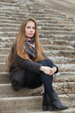 Lifestyle portrait of young and pretty adult woman with gorgeous long hair posing sitting on concrete stairway looking into camera. Hugging her knees Royalty Free Stock Image
