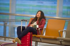 Young pretty tired and exhausted Asian Korean tourist woman in airport sleeping bored sitting at boarding gate hall waiting for de royalty free stock photography