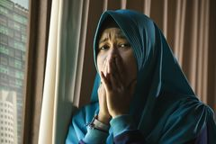 Young sad and depressed Muslim woman in Islam traditional Hijab head scarf at home window feeling unwell suffering depression. Lifestyle portrait of young sad royalty free stock photography