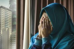 Young sad and depressed Muslim woman in Islam traditional Hijab head scarf at home window feeling unwell suffering depression. Lifestyle portrait of young sad royalty free stock images