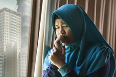 Young sad and depressed Muslim woman in Islam traditional Hijab head scarf at home window feeling unwell suffering depression. Lifestyle portrait of young sad stock photos