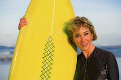Lifestyle portrait of young beautiful and happy surfer woman holding yellow surf board smiling cheerful enjoying summer holid. Ays in tropical beach wearing cool royalty free stock photos