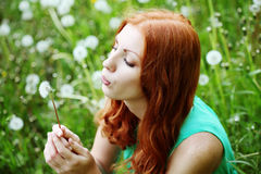 Lifestyle portrait of young spring fashion woman blowing dandelion in spring garden. Royalty Free Stock Photos