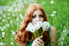 Lifestyle portrait of young spring fashion woman blowing dandelion in spring garden. Stock Photo