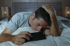 Lifestyle portrait of young tired and exhausted man sleeping or falling asleep while networking in bed late at night in internet. And social media smart phone royalty free stock images
