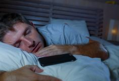 Lifestyle portrait of young tired and exhausted man sleeping or falling asleep while networking in bed late at night in internet. And social media smart phone stock photo