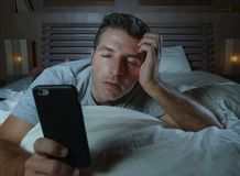 Lifestyle portrait of young tired and exhausted man sleeping or falling asleep while networking in bed late at night in internet. And social media smart phone stock photography