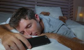 Lifestyle portrait of young tired and exhausted man sleeping or falling asleep while networking in bed late at night in internet. And social media smart phone stock image