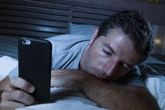 Lifestyle portrait of young tired and exhausted man sleeping or falling asleep while networking in bed late at night in internet. And social media smart phone stock photos