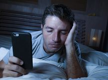 Lifestyle portrait of young tired and exhausted man sleeping or falling asleep while networking in bed late at night in internet. And social media smart phone royalty free stock photo