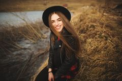 Lifestyle portrait of young woman in black hat resting by the lake on a nice and warm autumn day royalty free stock photography