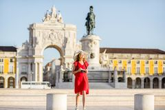 Woman traveling in Lisbon, Portugal. Lifestyle portrait of a young woman tourist walking on the main square with statue and triumphal arch on the background royalty free stock photo