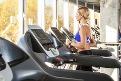 Lifestyle. Profile view of woman in sportswear jog on racetrack Stock Photos