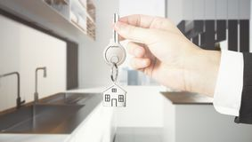 Lifestyle and purchase concept. Businessman hand holding abstract key with house keychain on blurry kitchen interior background. Lifestyle and purchase concept Stock Photography