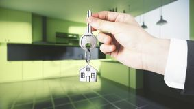 Lifestyle and realtor concept. Businessman hand holding abstract key with house keychain on blurry kitchen interior background. Lifestyle and realtor concept. 3D Stock Photography