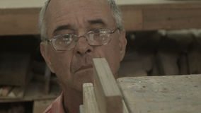 Lifestyle 50s-60s Man working indoors in hobby shed or workshop with carpentry p stock footage