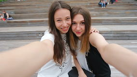 Lifestyle selfie portrait of two young positive woman having fun and making selfie. Concept of friendship and fun with stock video