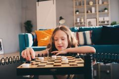 Lifestyle shot of smart kid girl playing checkers at home royalty free stock images