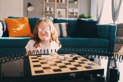 Lifestyle shot of smart kid girl playing checkers at home. Board games for kids concept, candid series with real people in modern interior royalty free stock image