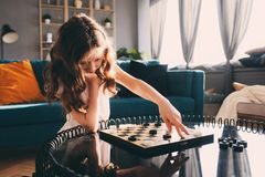 Lifestyle shot of smart kid girl playing checkers at home royalty free stock photos