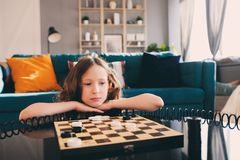 Lifestyle shot of smart kid girl playing checkers at home stock photo