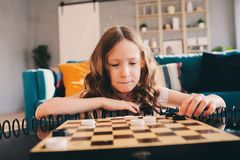 Lifestyle shot of smart kid girl playing checkers at home stock images