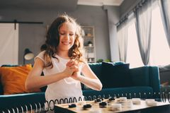 Lifestyle shot of smart kid girl playing checkers at home stock image